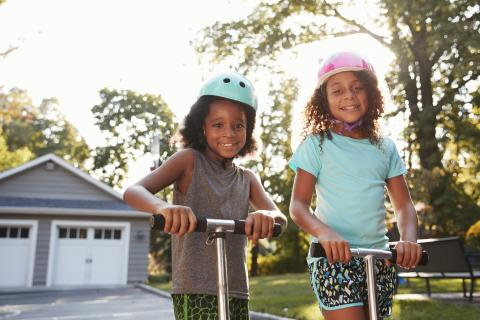 Two young girls playing on scooters in a driveway