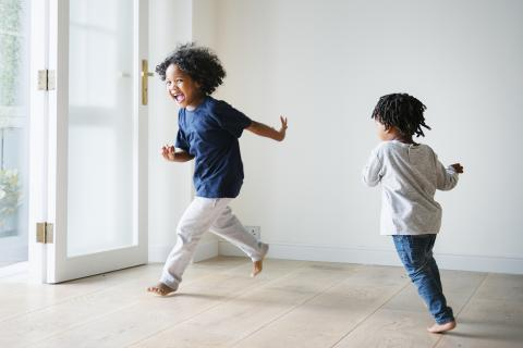 Younger brother chases older sibling around living room while playing