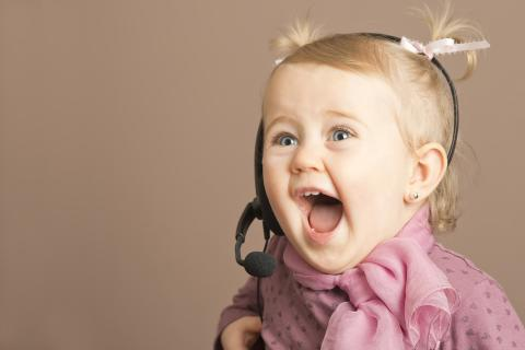 Young girl wearing headset, yelling gleefully