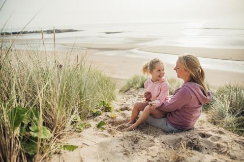 Daughter sits on mother's lap as they relax on a beach.
