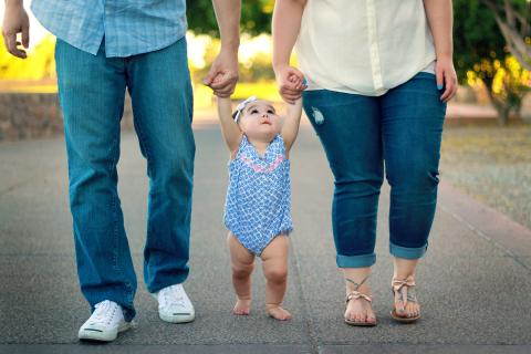 Two parents each hold one of their infant daughter's hands as they help her walk down a path.