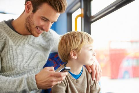 A father looks at his phone while riding the bus with his son.