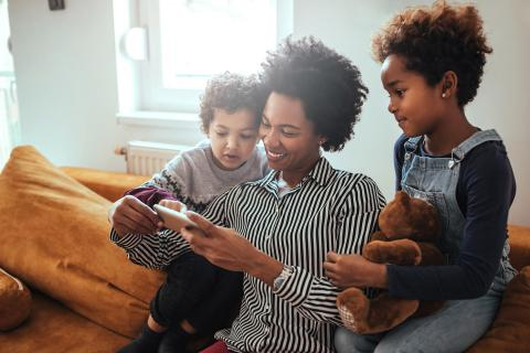 Mom and kids look at pictures on a phone while hanging out on the couch.