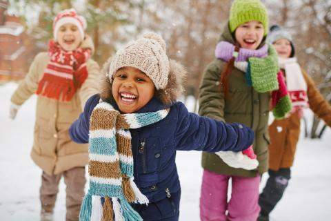 A group of children play together in the snow.