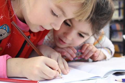 Two children draw together with colored pencils.