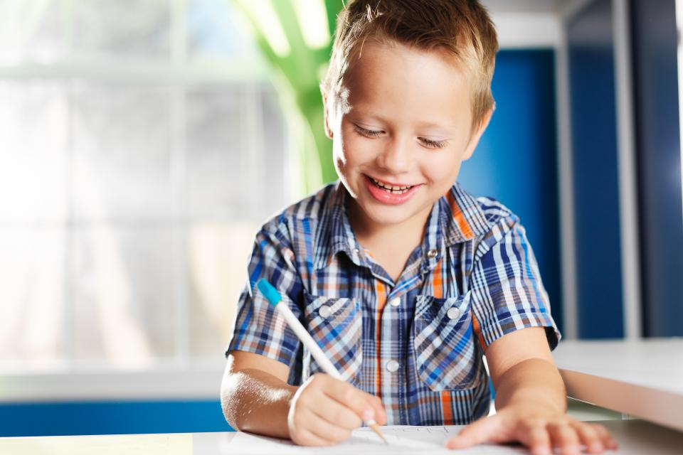 Smiling child sits at desk writing on a piece of paper.