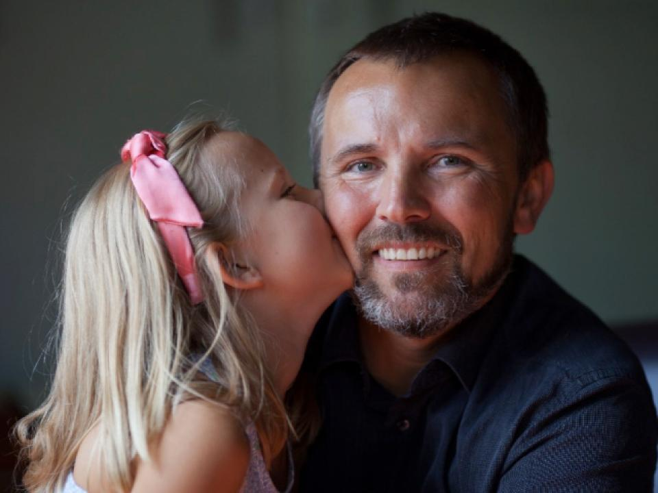 Daughter with a pink bow on her head kisses the cheek of her smiling father