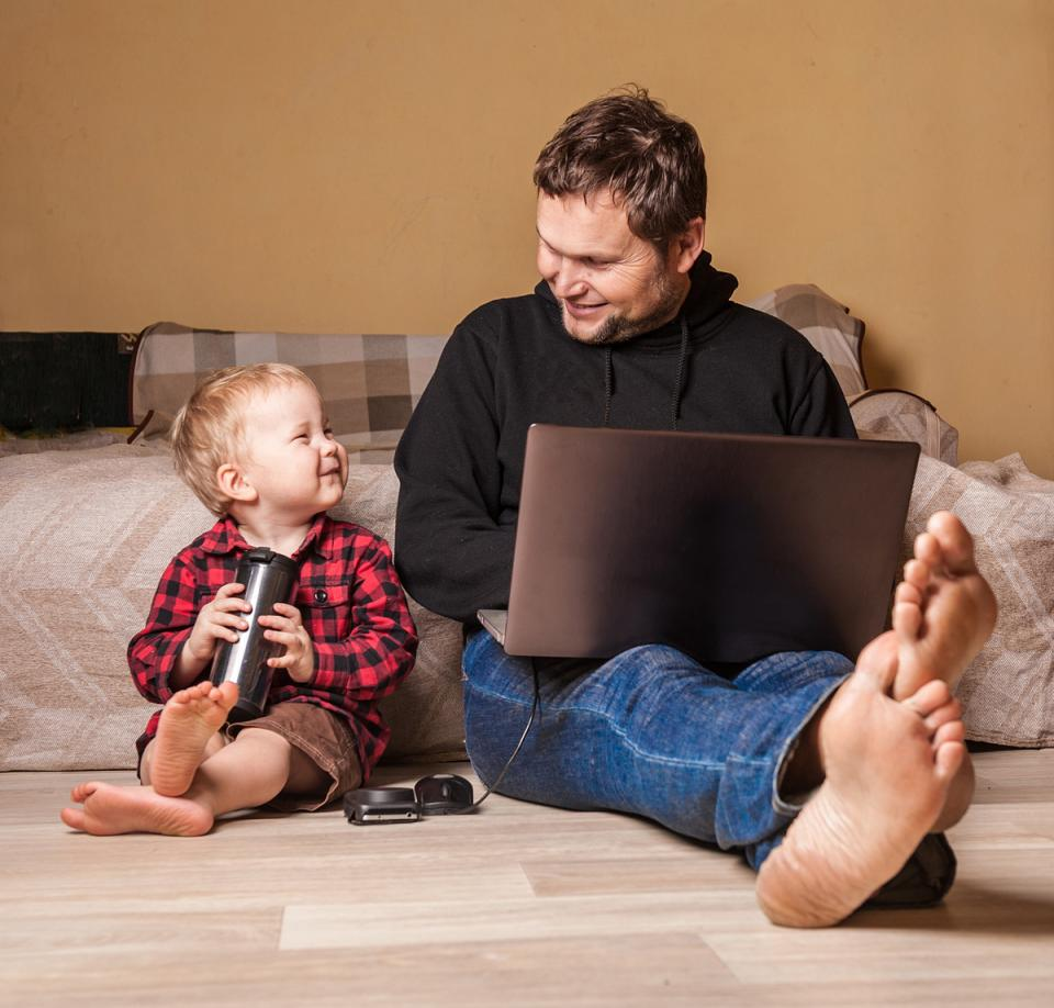 Father works on laptop as young son happily sits next to him.